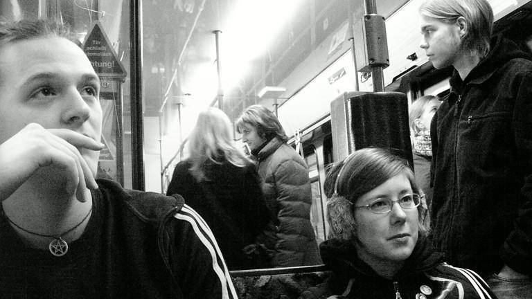 Menschen in einer Bahn gucken aneinander vorbei