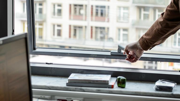 Eine Hand greift zum Bürofenster um es zu öffnen.