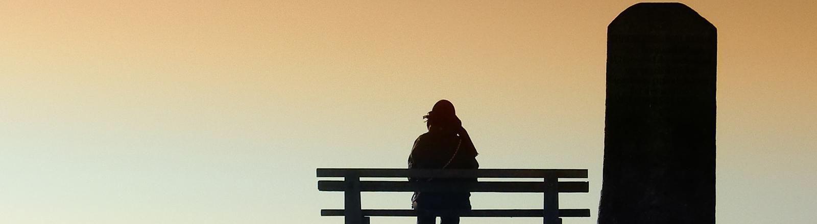 Ein Mensch sitzt einsam auf einer Bank und blickt in den Sonnenuntergang, neben ihm ein hoher Grabstein