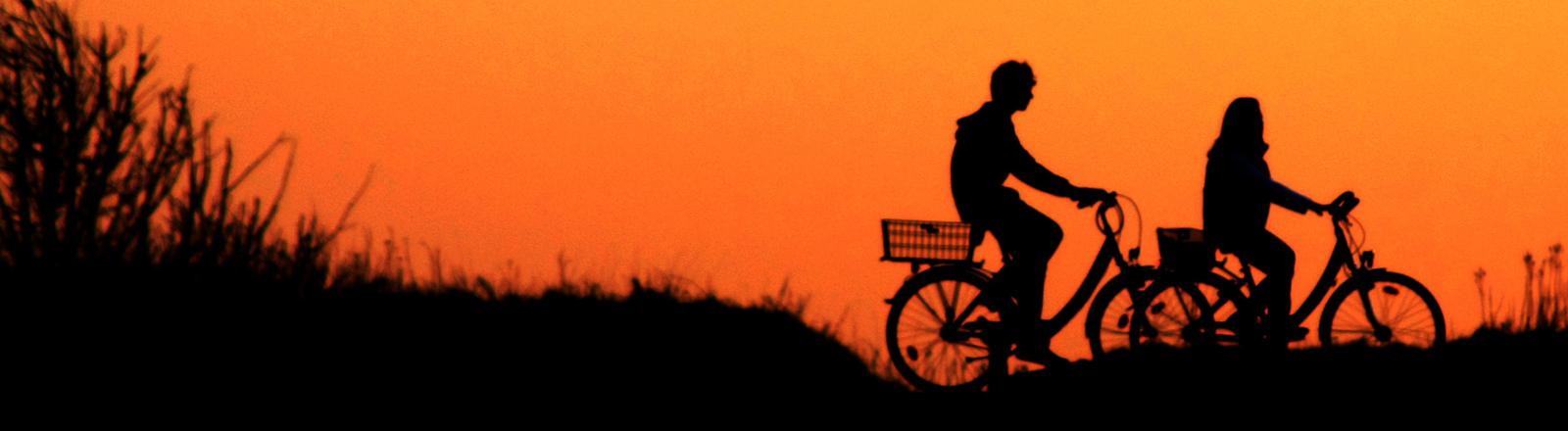 Zwei Radfahrer bei Sonnenuntergang auf einer Düne