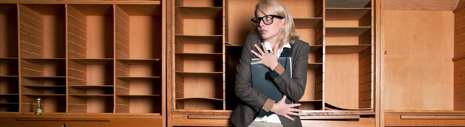 Eine Frau steht vor einem leeren Regal und klammert sich an ihren Akten fest