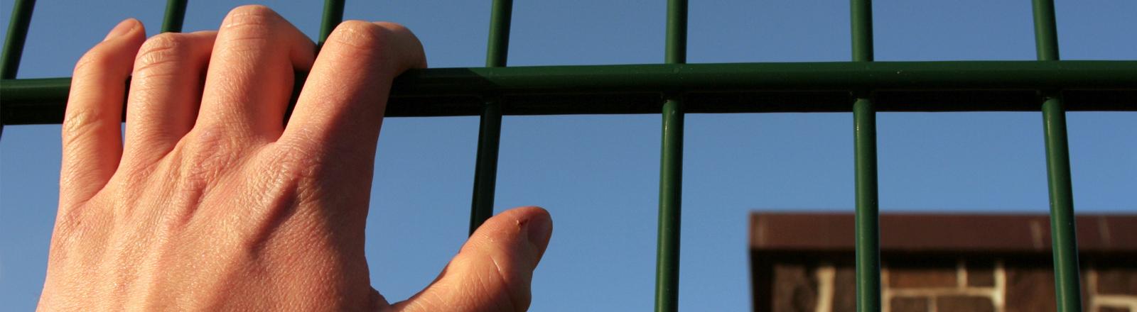 Eine Hand greift an ein Gitter
