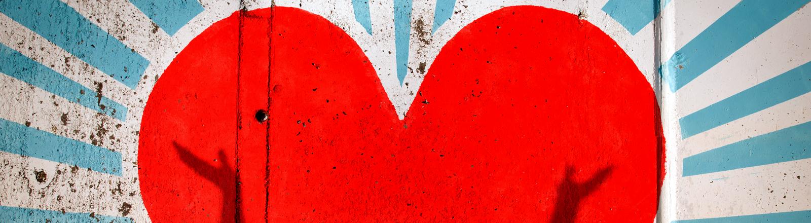Ein Grafitti Herz, davor ein Schatten, der die Hände in die Luft hebt