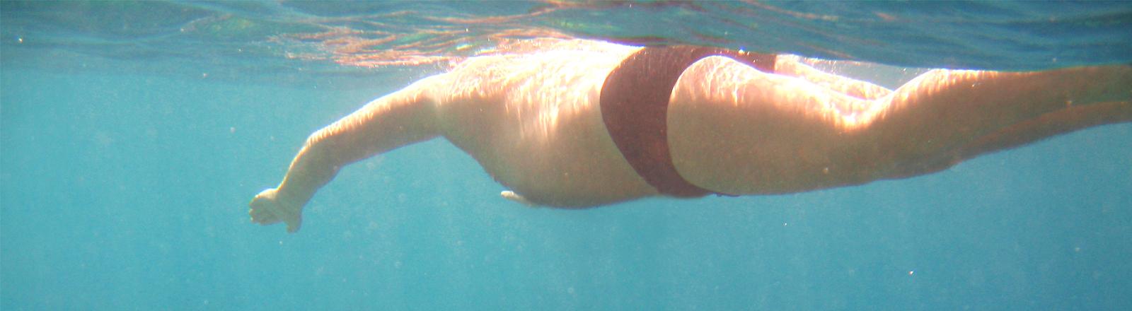 Ein Mann mit weicheren Körperformen beim Schwimmen