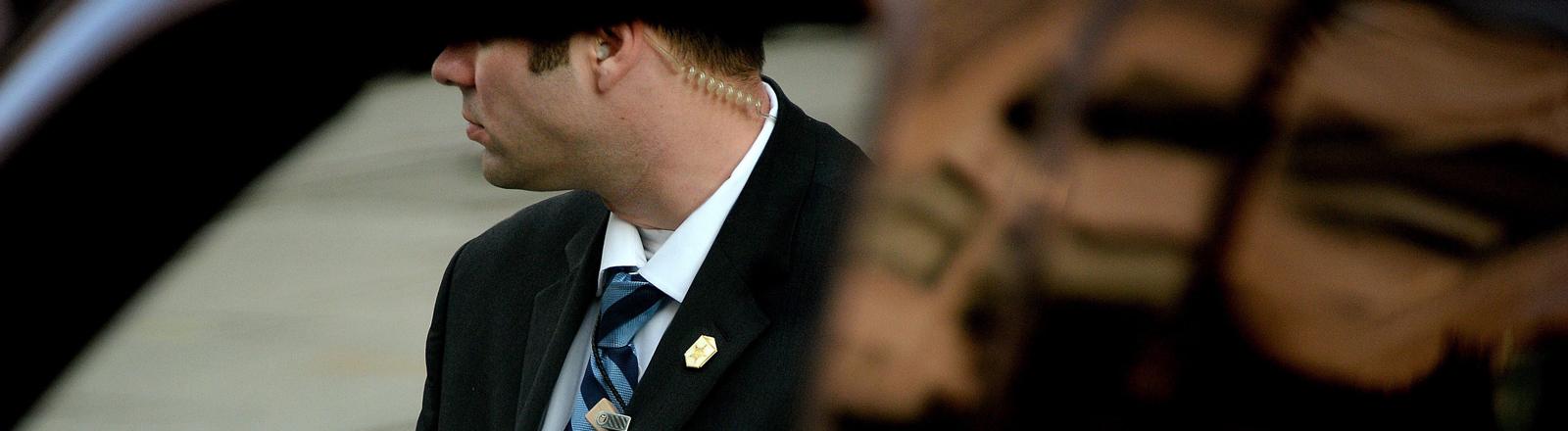 Mann mit einem Knopf im Ohr.