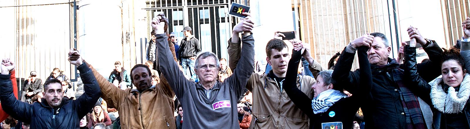 Menschen in Brüssel halten sich an den Händen