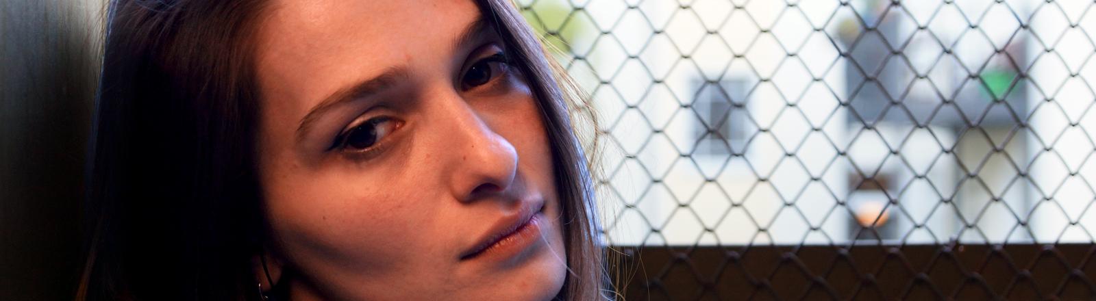 Kristina Sheli in einem Aufzug mit Gittern im Hintergrund