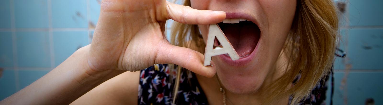 Eine Frau hält den Buchstaben A vor ihren offenen Mund