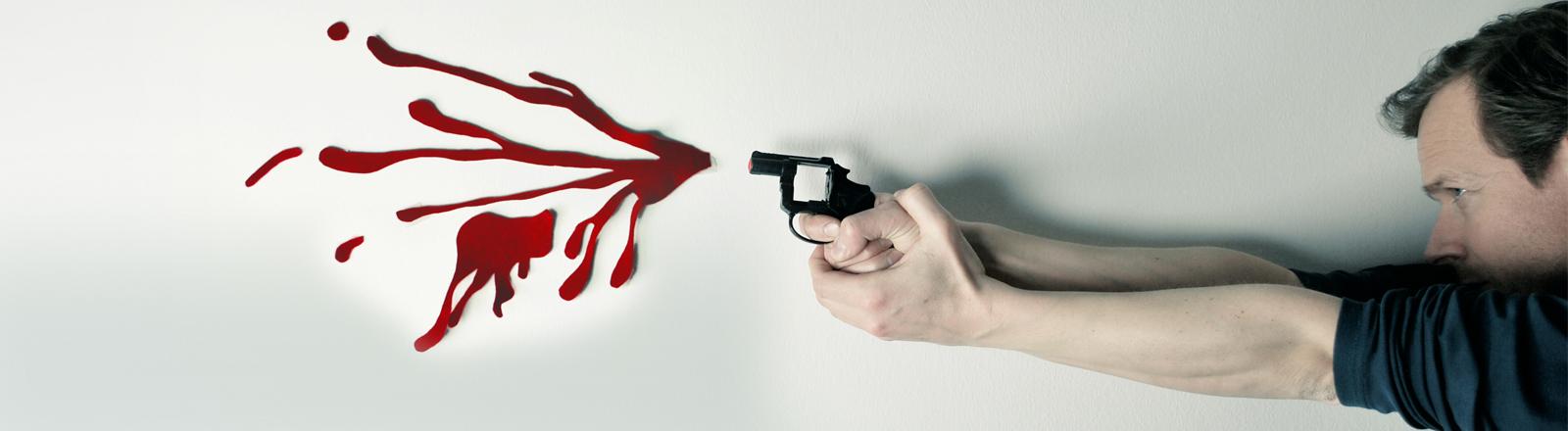 Ein Mann schießt aus einem kleinen Revolver ohne Magazin - auf der Wand hängen aus Papier geschnittene Blutspritzer