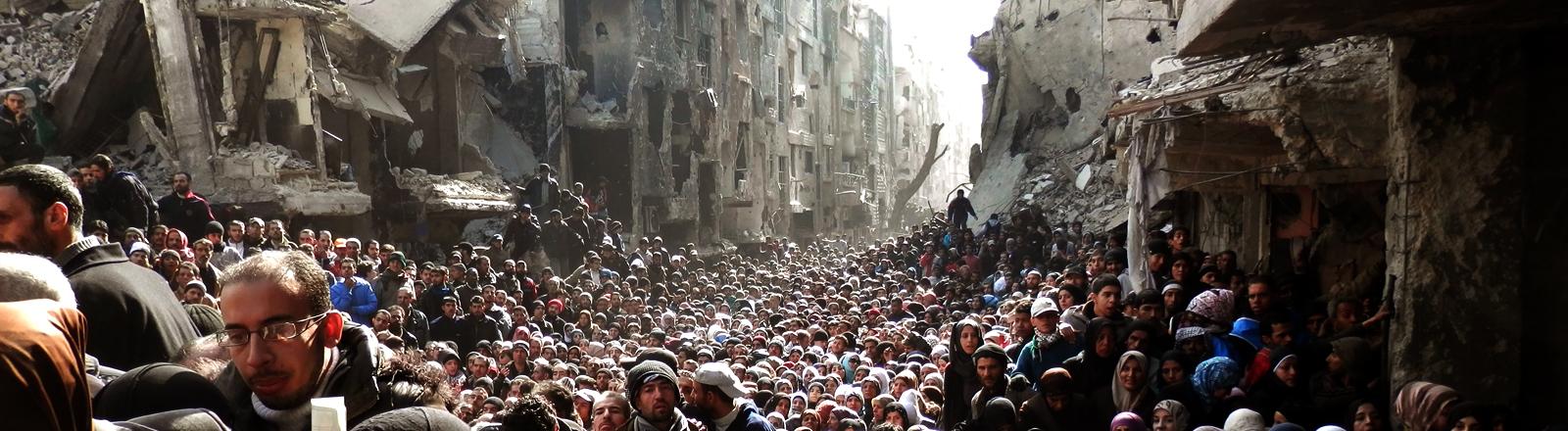 Zahllose Menschen stehen dicht gedrängt in einer Straße zwischen zerstörten Häusern.