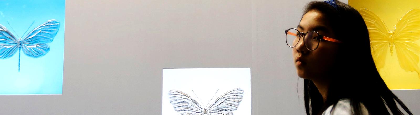 Eine Besucherin geht an den Schmetterlingen von Damien Hirst vorbei