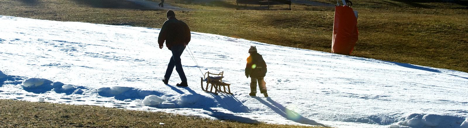 Ein Mann und ein Kind gehen einen Hügel hoch, auf dem Schnee liegt - rundherum ist grüne Wiese