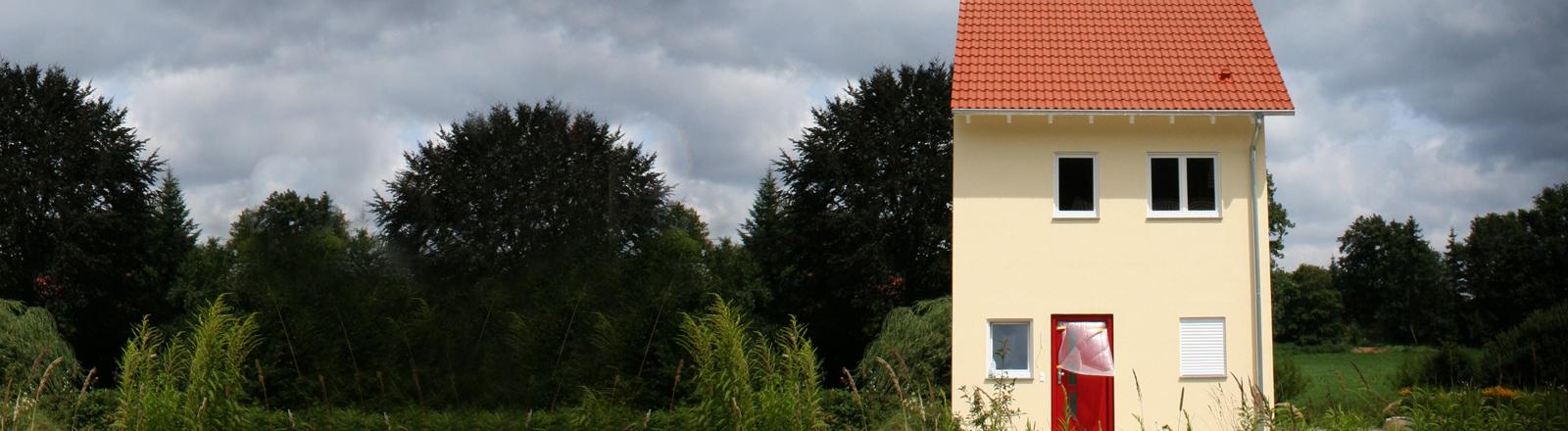 Eine halbe Doppelhaushälfte steht irgendwo frei auf dem Feld