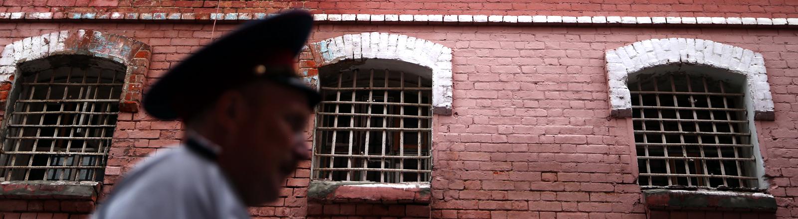 Vor einem Gefängnis in Russland geht ein russischer Polizeibeamter vorbei