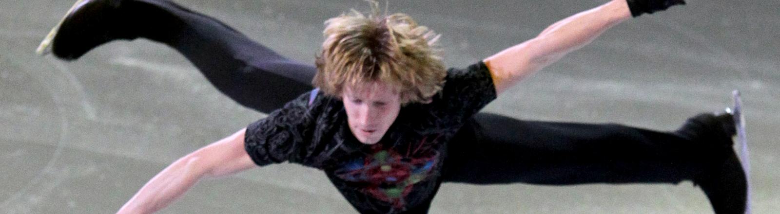 Ein Mann springt auf Schlitschuhen in die Luft