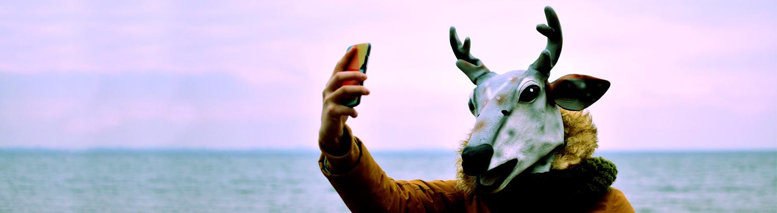 Ein Mann in einer Hirschmaske fotografiert sich selber