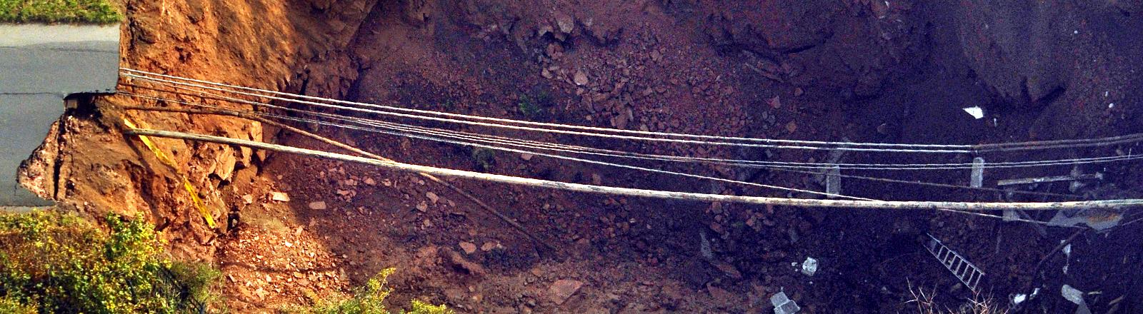Ein Erdloch, darüber verlaufen mehrere Leitungen und Rohre, die unter einer Straße verlegt waren.