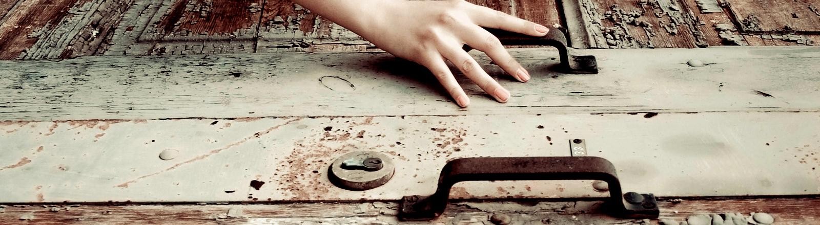 Eine Hand versucht, eine alte, rostige Tür zu öffnen