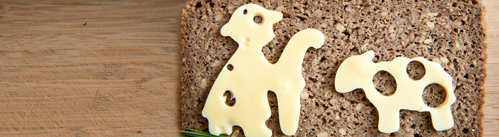 Auf einer Scheibe Vollkornbrot liegt eine Scheibe Käse in der Form eines Lamms