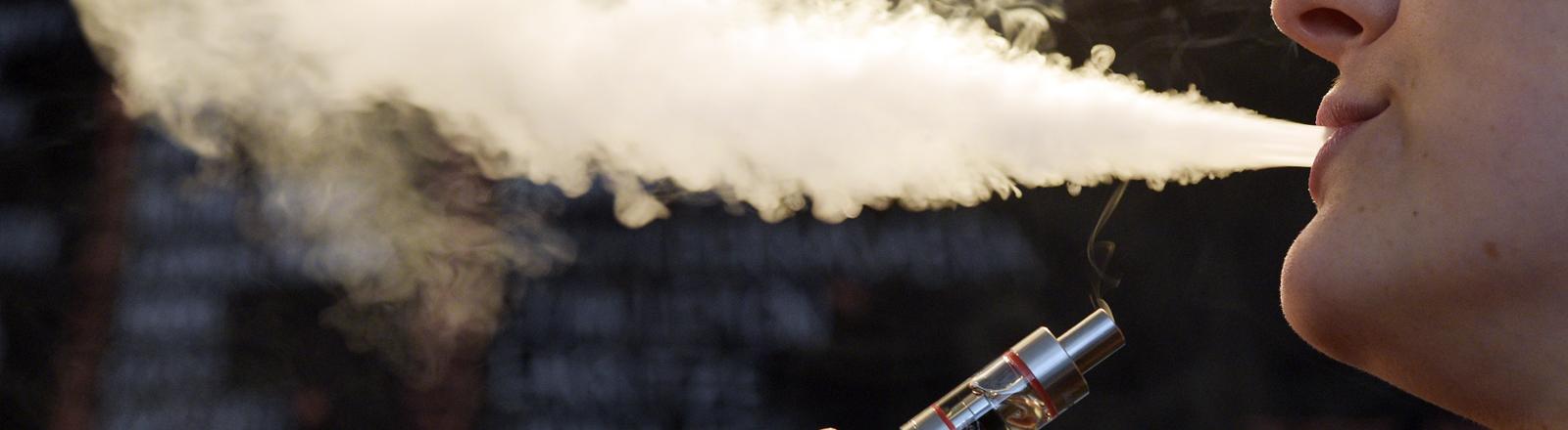 Eine Frau pustet den Rauch einer E-Zigarette aus