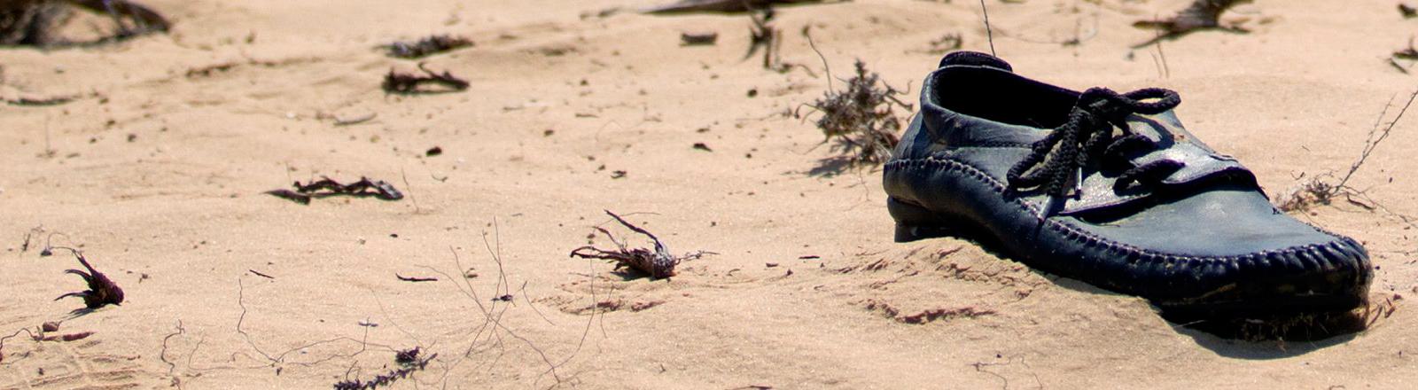 Ein einzelner Schuh liegt im Wüstensand