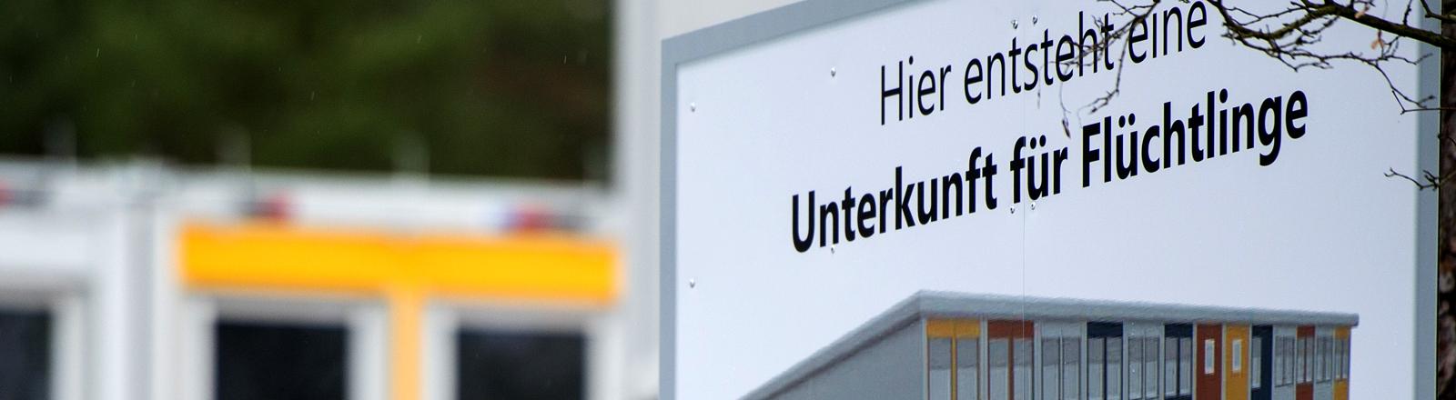 Auf einem Schild steht eine Füchtlingsunterkunft als Containerbau abgebildet.