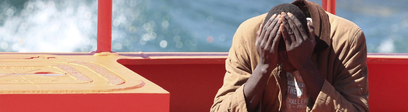 Ein Mann, der gerade von einem Flüchtlingsboot gerettet wurde, hat den Kopf in den Händen vergraben