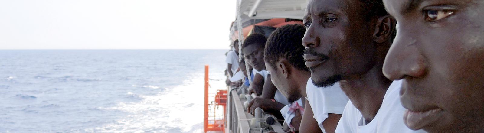 Schwarze Männer auf einem Boot im Meer