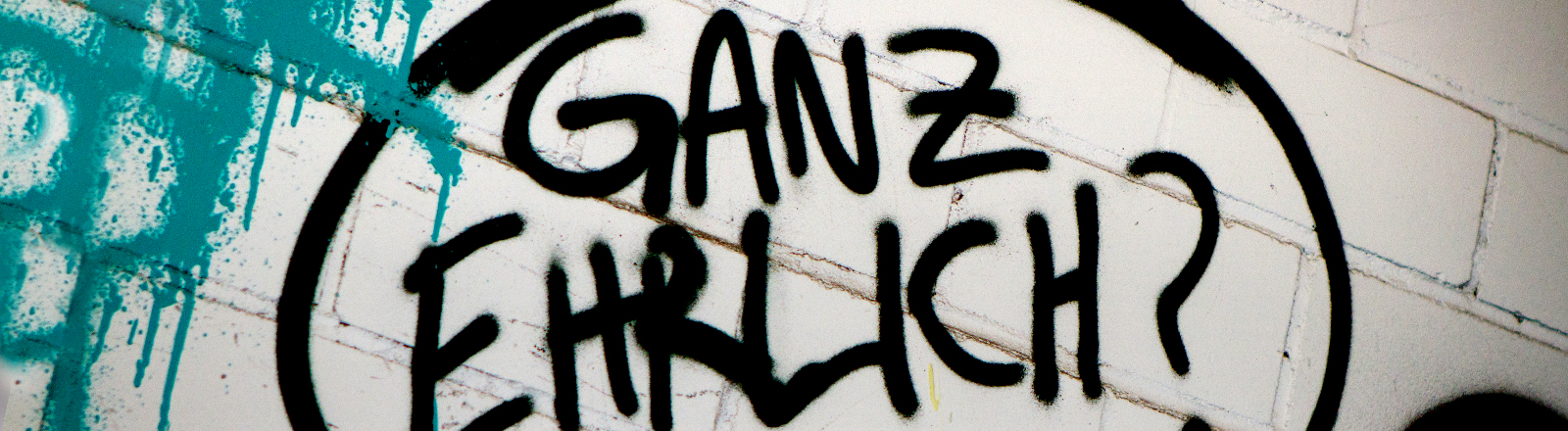 Auf eine weiße Wand hat jemand die Worte: ganz ehrlich? gesprüht.