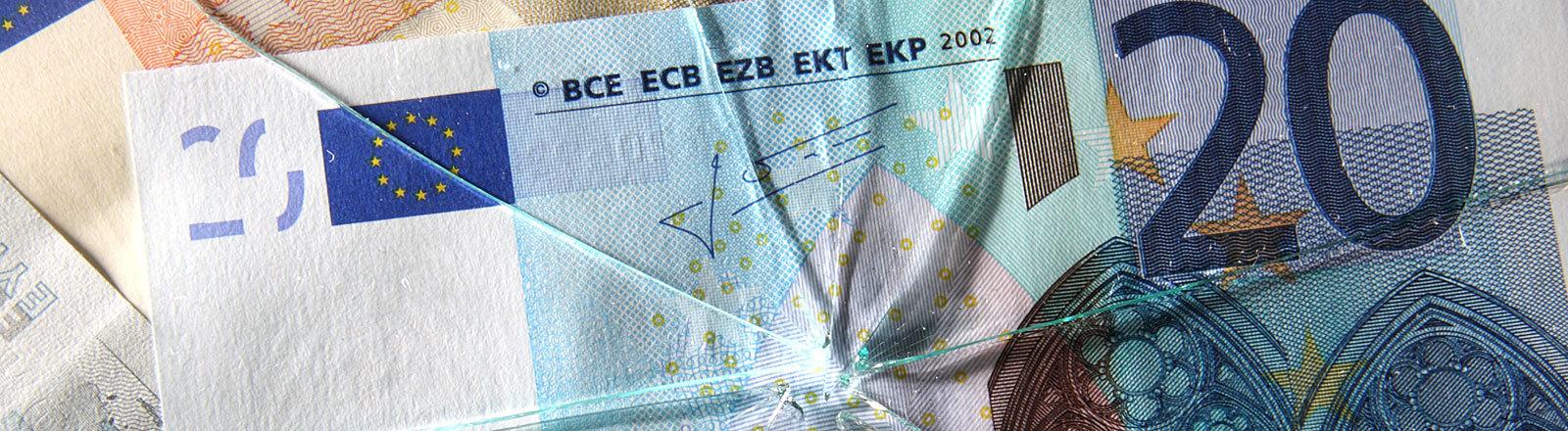 Euro-Geldscheine unter einer zersplitterten Glasscheibe