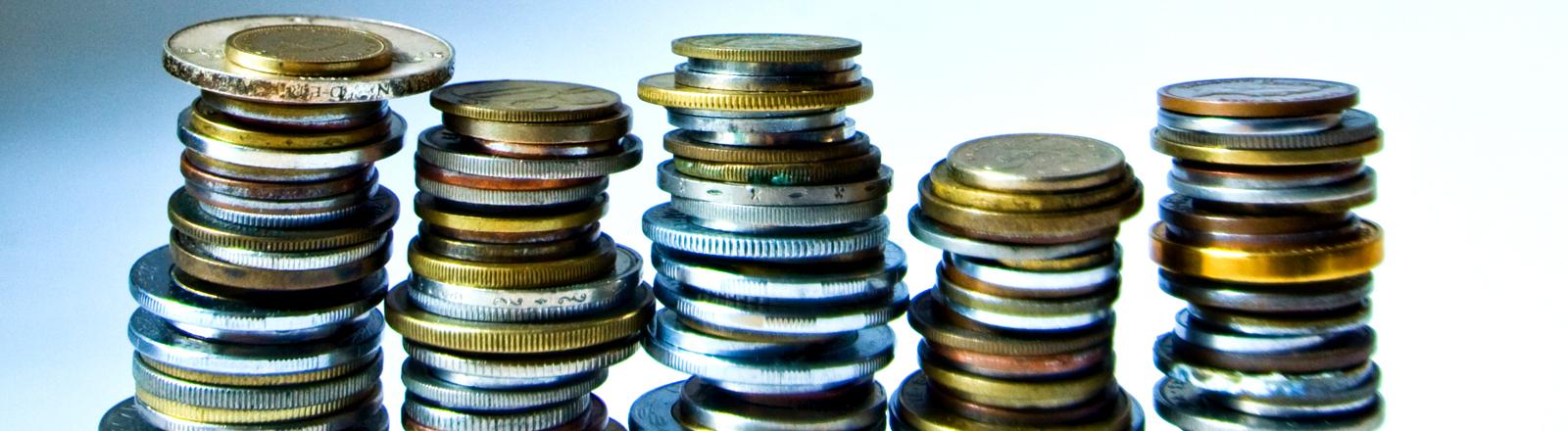 Fünf Stapel mit verschiedenen Münzen ungefähr gleich hoch