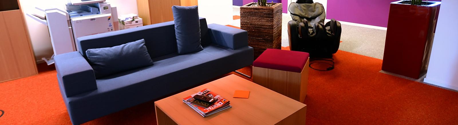 Im Hintergrund steht ein Kopierer, der Rest erinnert an ein Wohnzimmer: bunte Wände, eine Couch, Pflanzen, Teppichboden und ein Massagesessel.