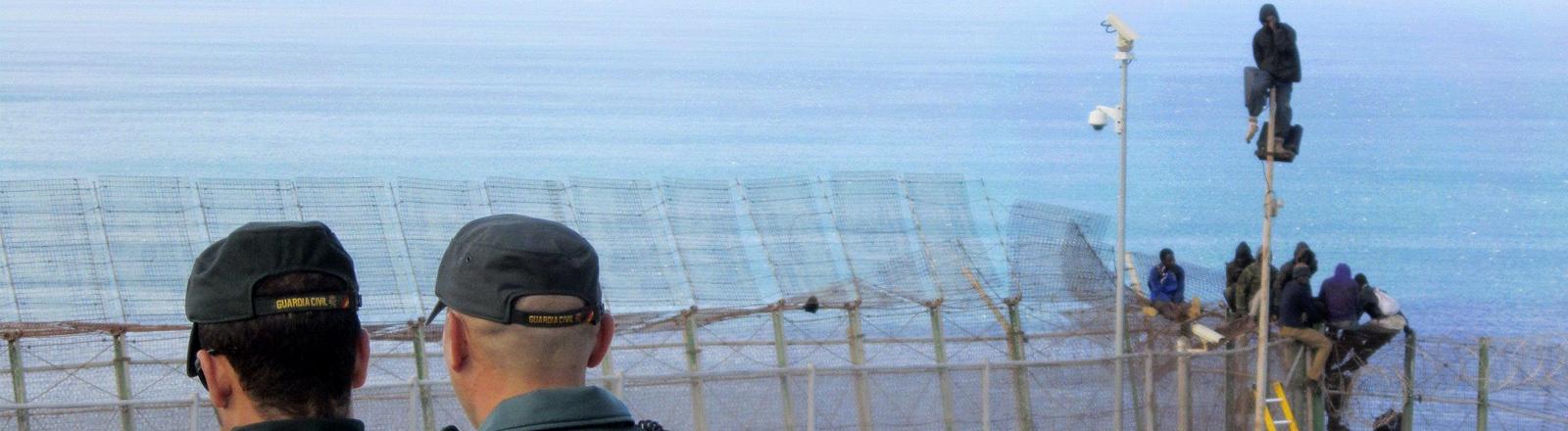 Zwei Flüchtlinge sitzen auf einem Zaun in Melilla