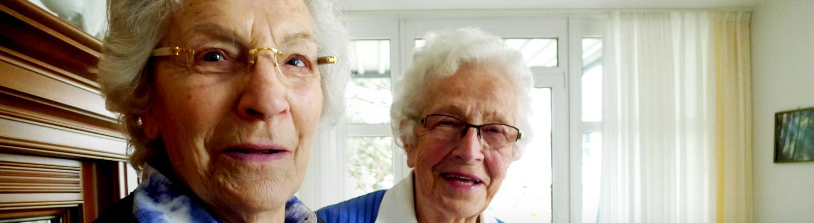 Zwei ältere Damen grinsen und drohen spaßeshalber mit erhobenem Zeigefinger