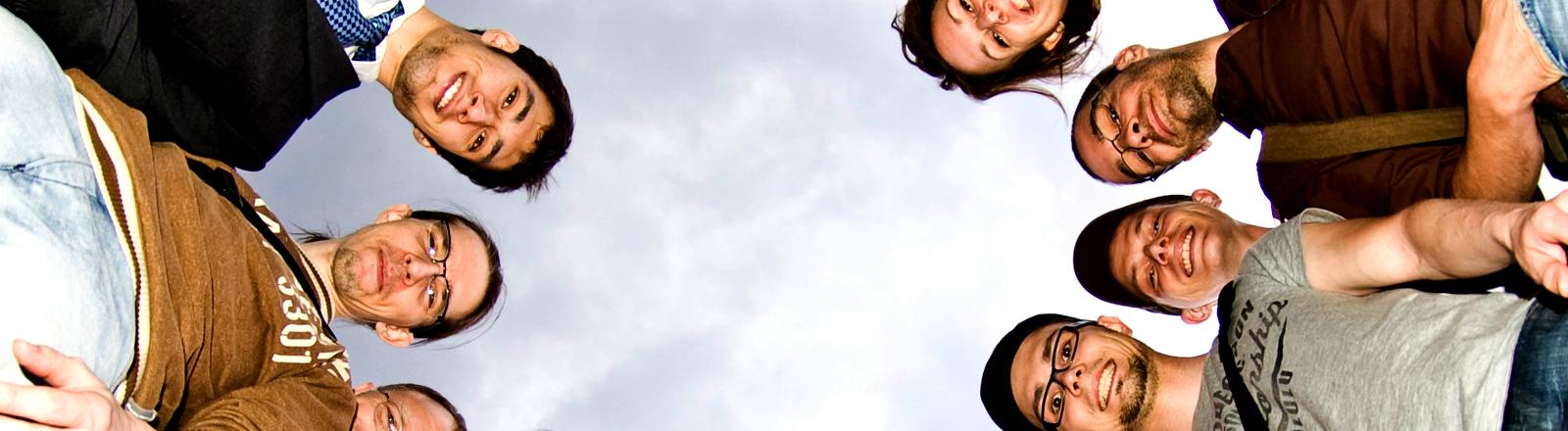 Eine Gruppe von Menschen steht im Kreis und blickt lächend von oben in eine auf dem Boden liegende Kamera