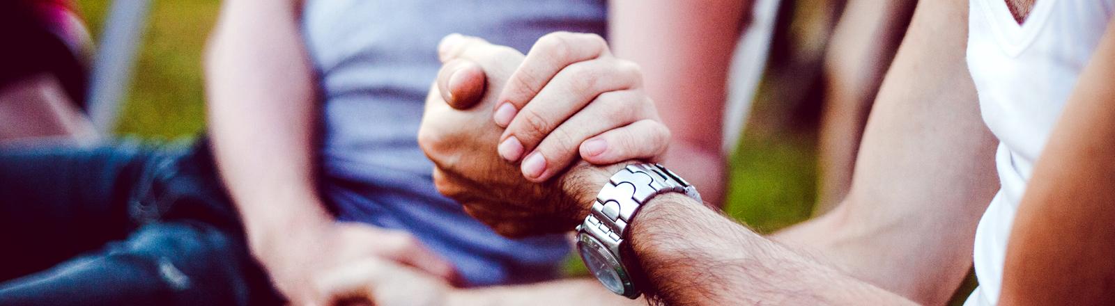 Zwei Männer auf einer Parkbank begrüßen sich mit Handschlag