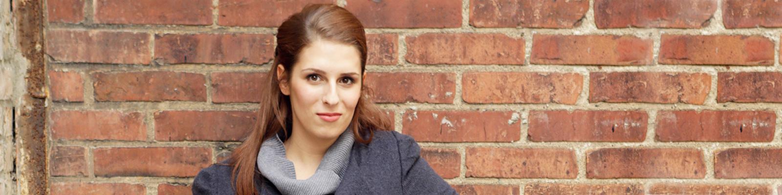 Hannah Winkler, eine junge Frau mit langen, braunen Haaren lehnt an einer Backsteinwand