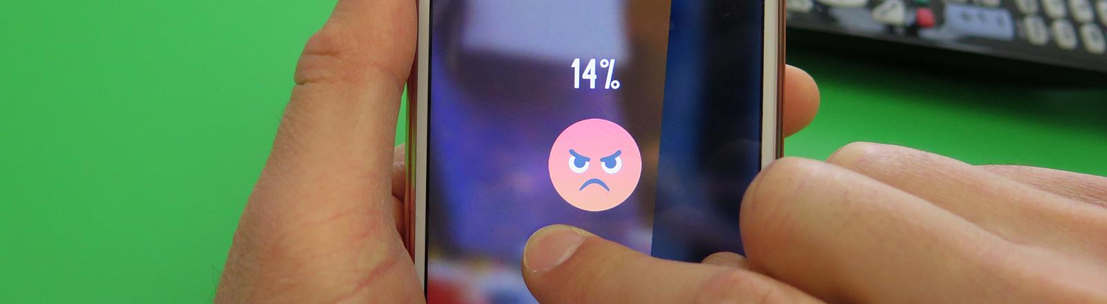 Auf einem Handy sieht man ein Hass-Emoticon