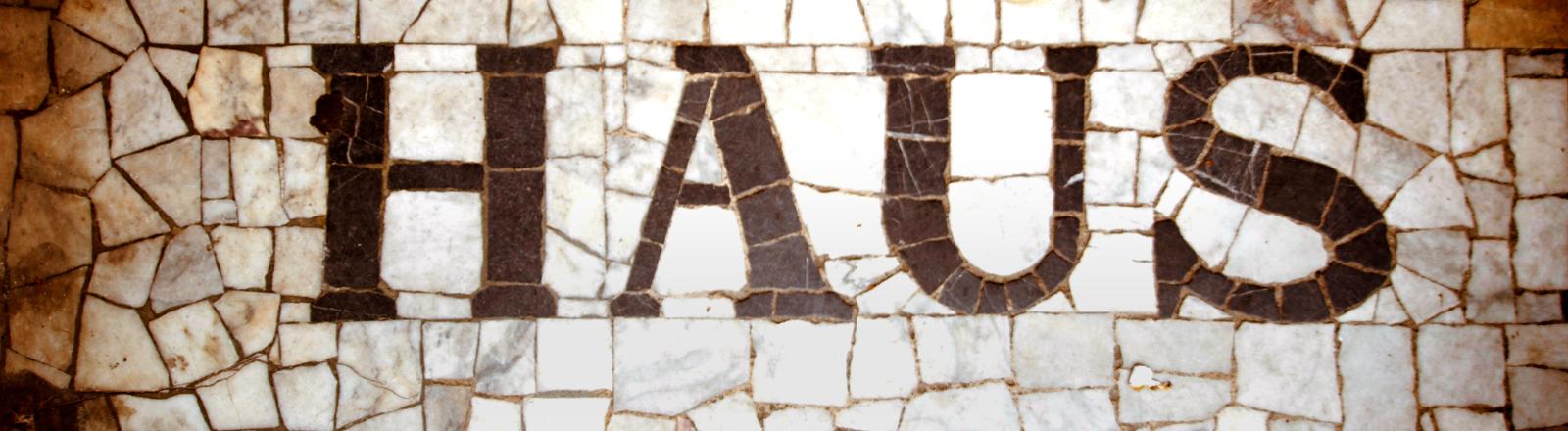 Ein Steinmosaik auf dem Haus steht