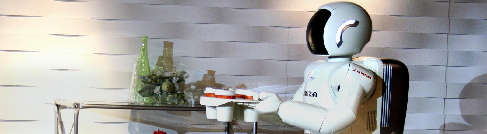 Ein dem Menschen nachempfundener Roboter serviert vier Becher Kaffee in einer Tragevorrichtung, Bild: dpa