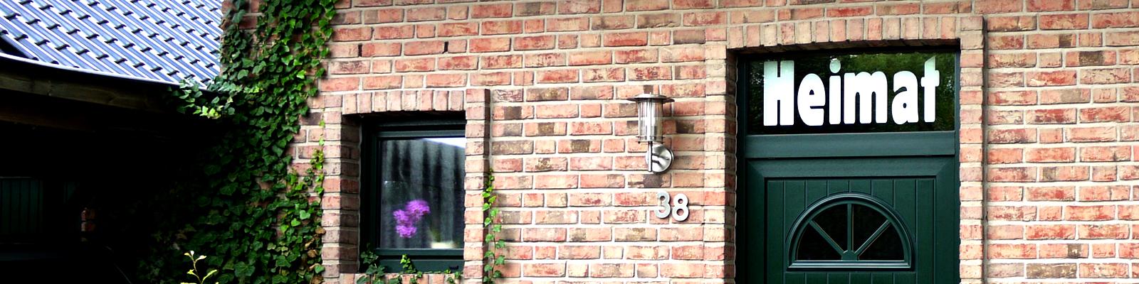 Im Fenster einer Haustür steht Heimat