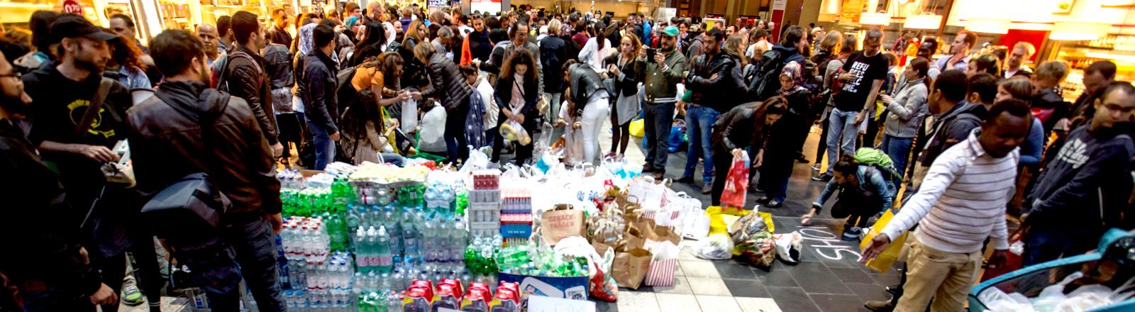 Mit Wasser und Tüten voller Essen werden Flüchtlinge am Frankfurter Hauptbahnhof empfangen