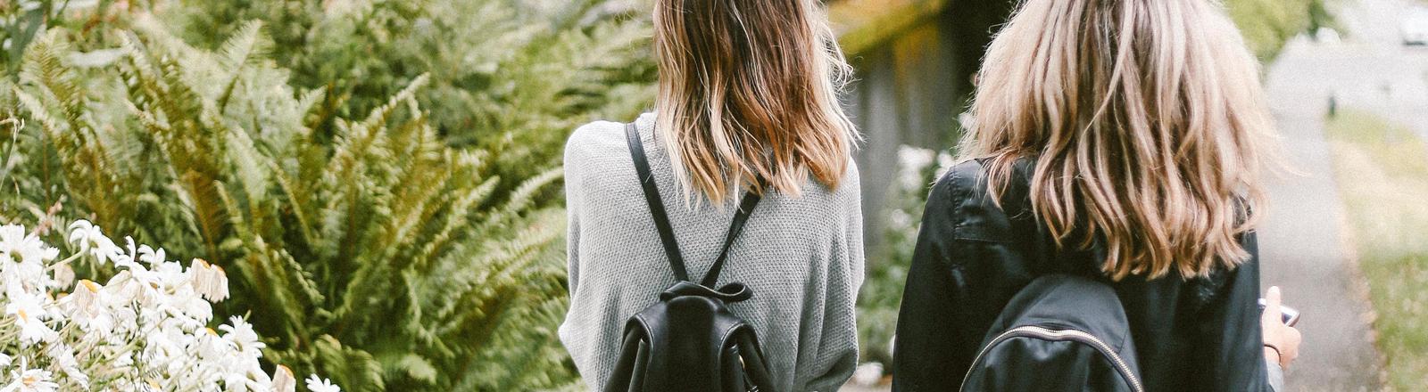Zwei Mädchen mit den gleichen Frisuren und ähnlichen Rucksäcken gehen nebeneinander her