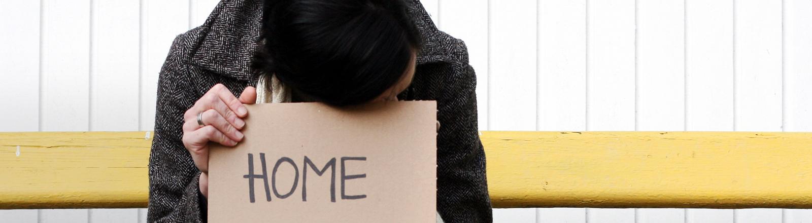 Eine Frau sitzt auf einer Bank und hat ein Schild auf dem Schoß, auf dem Home steht