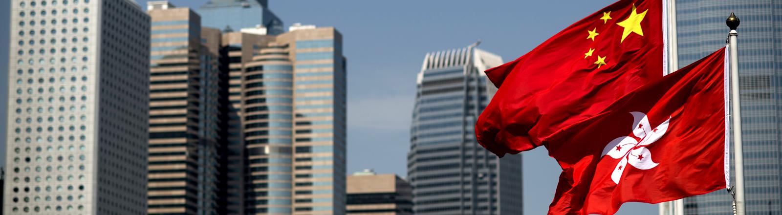 Die Flaggen von Hongkong und China vor einer Landschaft aus Hochhäusern