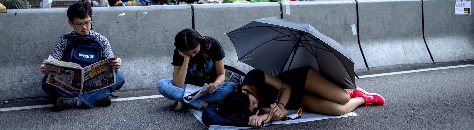 Menschen liegen und sitzen auf einer Hauptverkehrsstraße in Hongkong