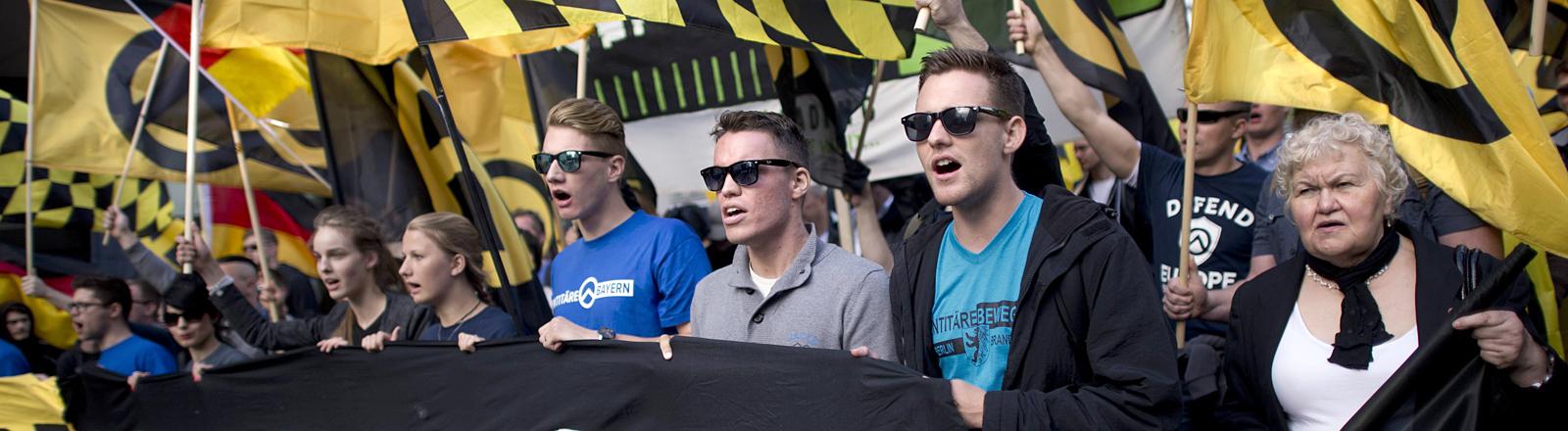 Menschen mit gelb-schwarzen Fahnen