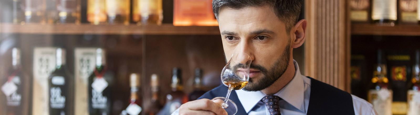 Elegant gekleideter Barkeeper, der an einem Whisky riecht.