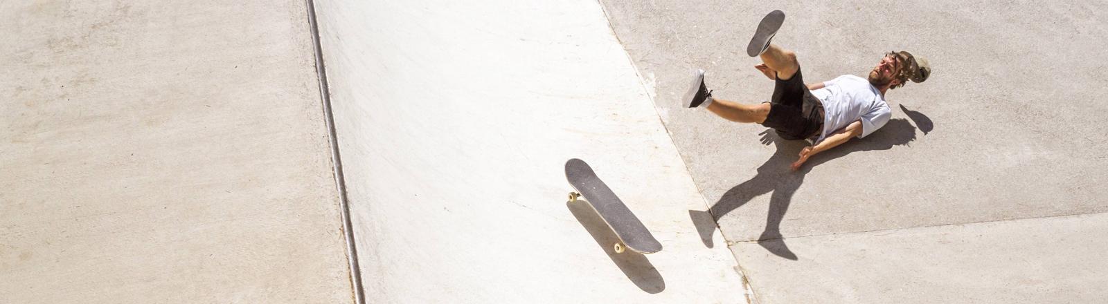 Mann stürzt mit Skateboard