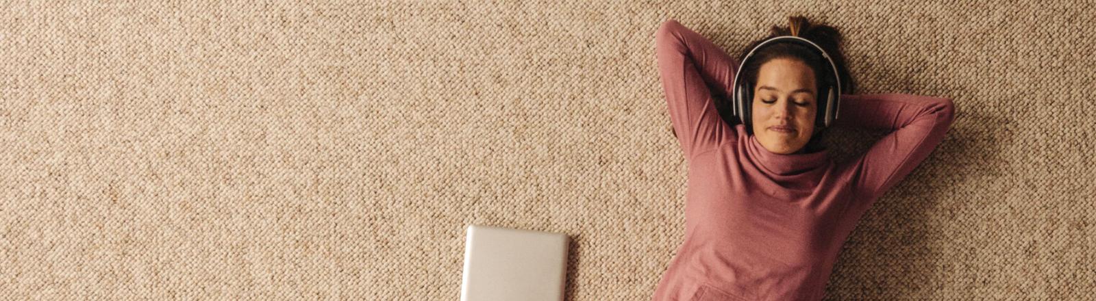 Frau liegt auf dem Teppich und hört über Kopfhörer Musik. Ihre Augen sind geschlossen.